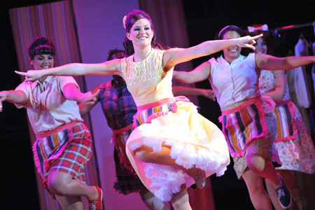 "Students dance in unison during a performance of the play ""Hairspray."""