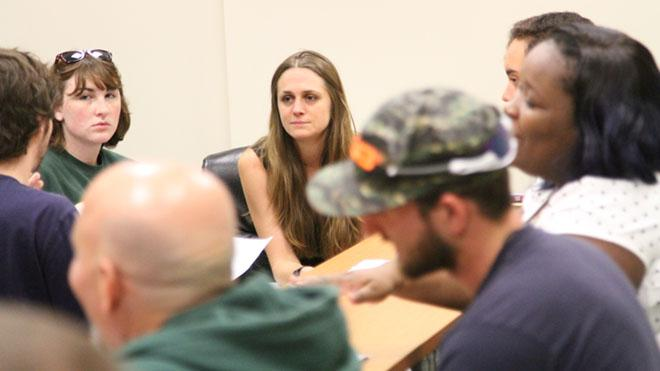 Picture of associate professor of history Julia Irwin sitting in a circle with others during a presentation.