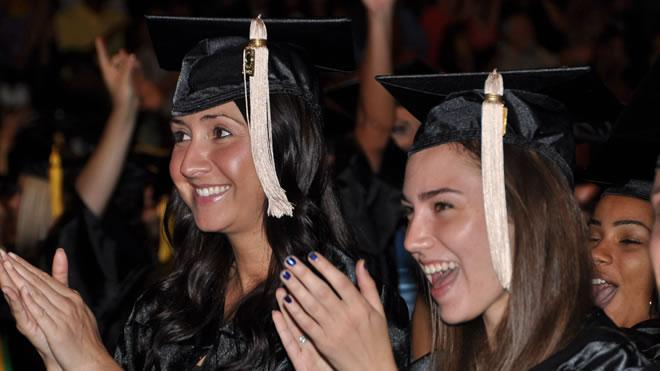 Two students with graduation caps clapping and smiling.