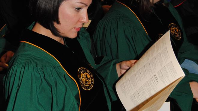Graduate in green gown reading program during graduation.
