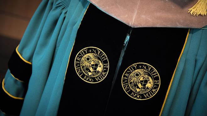 A picture of a green and black USF graduation gown.