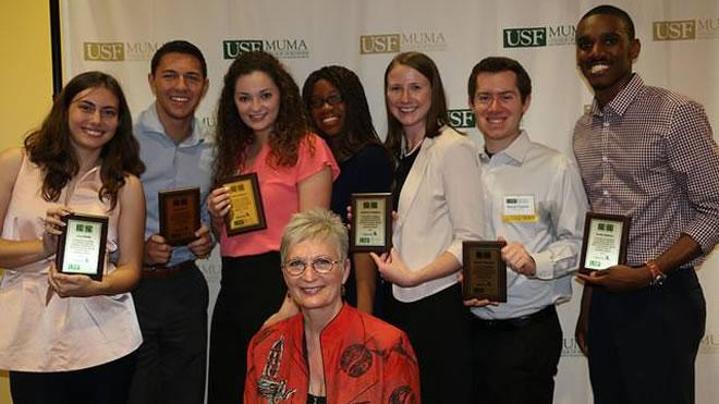 Picture of seven Business Honors students holding awards for 25 under 25.