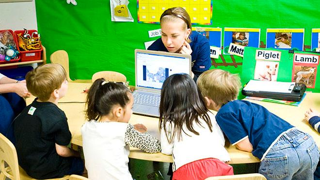 USF Speech Language Pathologist showing children something on a computer.