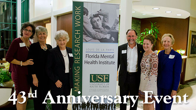 A group of older men and women taking a picture in front of a Florida Mental Health Institute image at the 43rd Anniversary Event