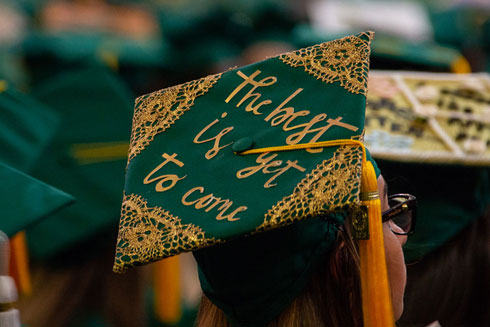 "Grad cap with ""the best is yet to come"" in gold lettering"