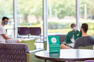 Three USF students in the Marshall Student Center on the Tampa campus with a new sign explaining the 6ft. distancing COVID-19 protocol on a table in the foreground.