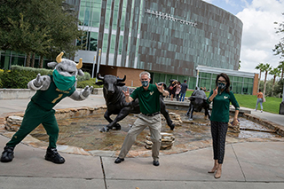 Rocky, President Currall, and Dr. Cheyenne Currall wearing USF face coverings and practicing physical distancing in front of the Marshall Student Center on the Tampa campus.
