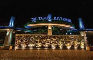 Sign for the Tampa Riverwalk lit up at night