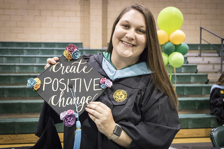 Student with decorated graduation cap that says create positive change