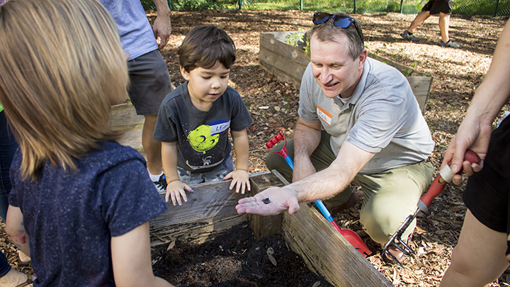 Dean Robert Knoeppel works with preschool students while preparing soil for a community garden
