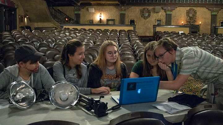 Camp counselor helps students edit their film project