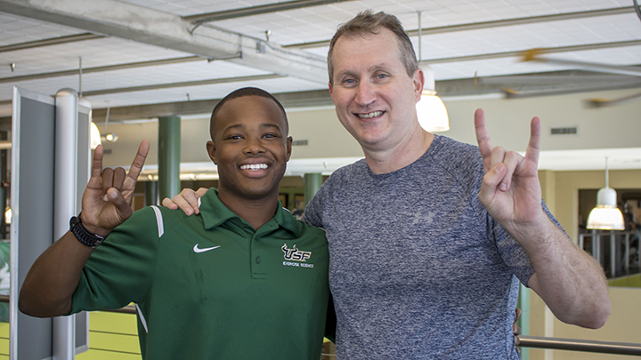 USF senior Joseph McMiller gives the USF Horns Up with College of Education Dean Robert Knoeppel