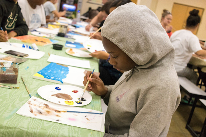 Student paints during art class at Pepin Summer Institute