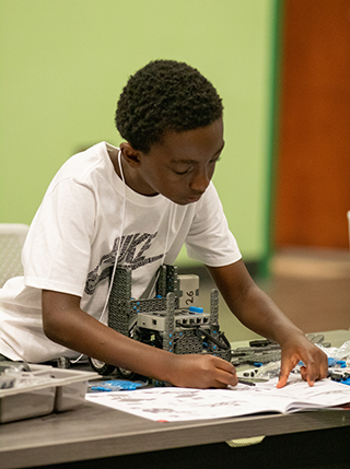Boy building a VEX IQ robot at USF Robotics Summer Camp