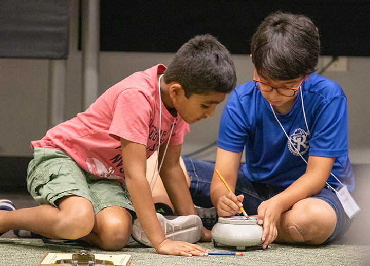 Boys programming a Roamer robot at the USF Robotics Summer Camp
