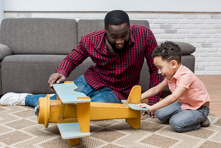Father and son playing with toys at home