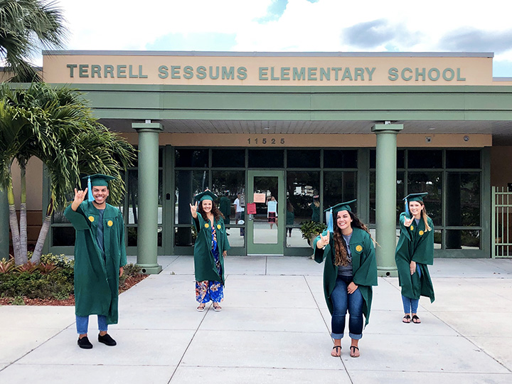 USF students in regalia outside of Sessums Elementary
