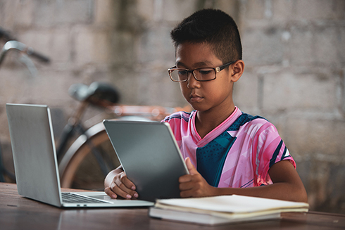 Child using laptop and tablet