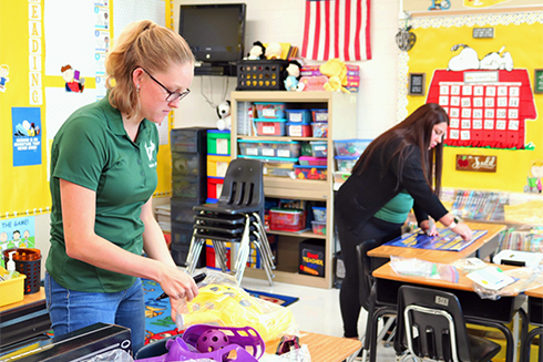 USF student and collaborating teacher setting up a classroom together