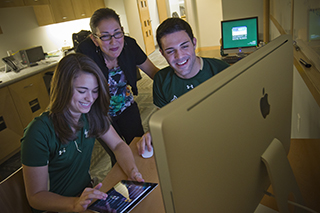 Students learning at a computer with a tutor
