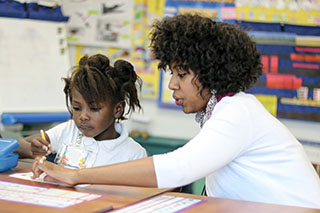 Counselor Education student helps a student during a lesson