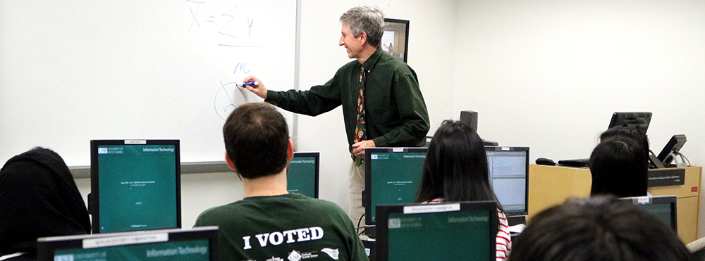 Faculty member teaching in the front of the classroom