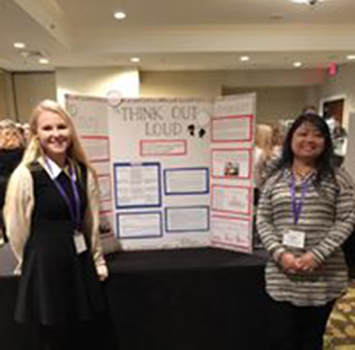 Students in front of presentation at conference