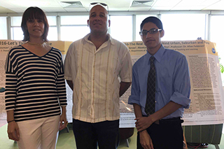 Javier Arias and Stephanie Baumann with student Frederick Bradley in front of project