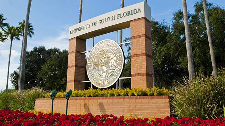 USF entrance with seal and red flowers blooming