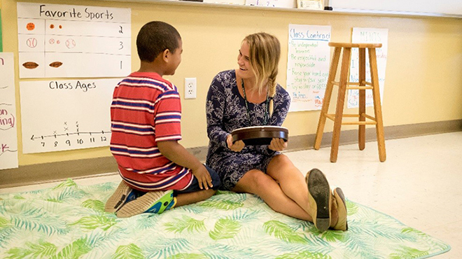 USF teacher candidate works with a student during music class