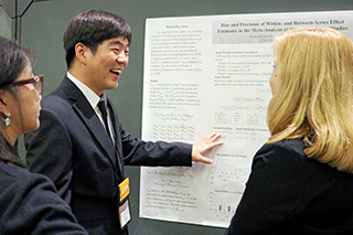 Graduate student giving poster presentation at a research conference