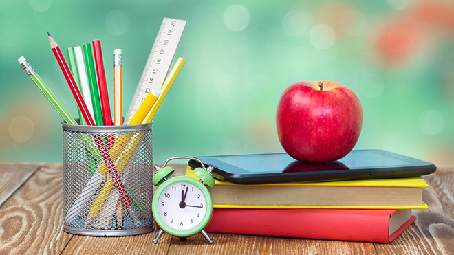 Apple and school supplies in a classroom