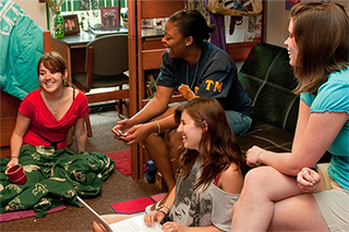 group of students laughing together in a dormroom