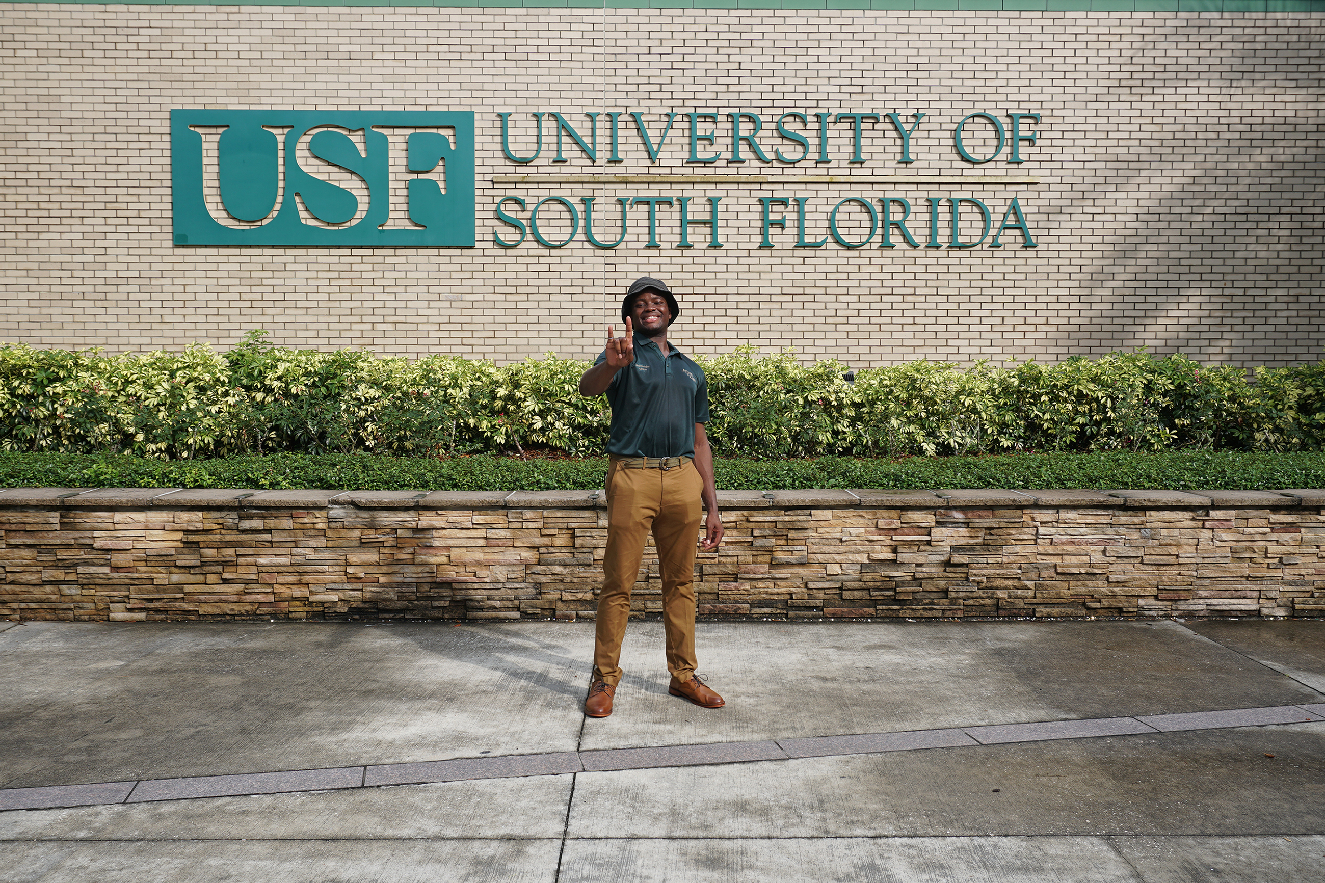 Ossie Douglas in front of the USF sign by the USF Bookstore