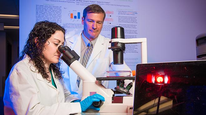 Picture of a USF female researcher looking through a microscope as her professor observes.
