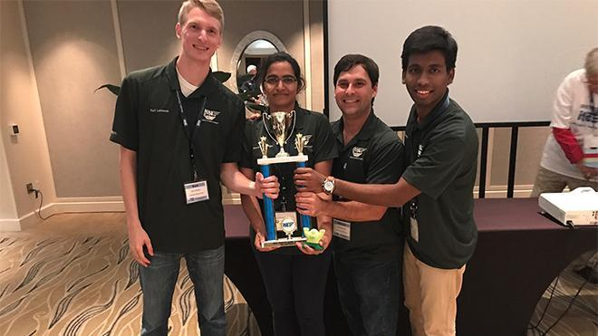 Picture of four USF Institute of Traffic Engineers students holding a trophy