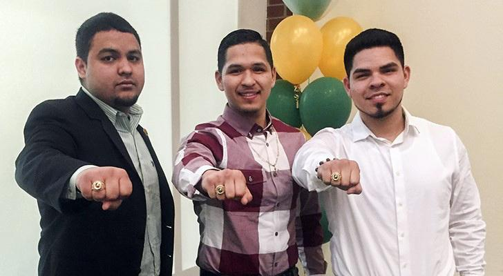 Picture of three Guzman-Ramos brothers showing of their rings before graduation.
