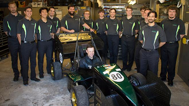 Picture of Matt Kenseth sitting in a race carat the SAE garage with USF students