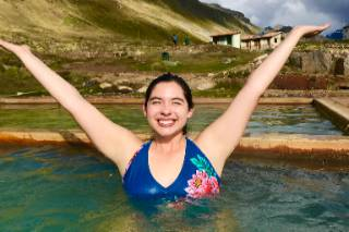Picture of a woman in a blue swimswui lifting her arms