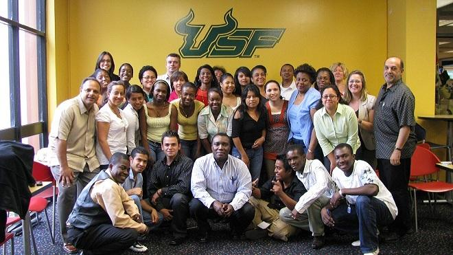 Group of USF students take a picture in front of a yellow wall with the USF logo.