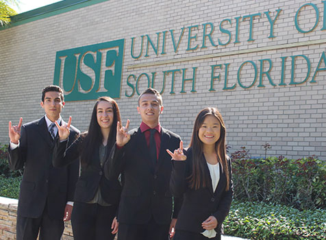 Students who were awarded scholarships to study at Oxford pose in front of the USF campus sign