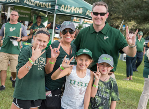 Parents and children in USF gear put their horns up