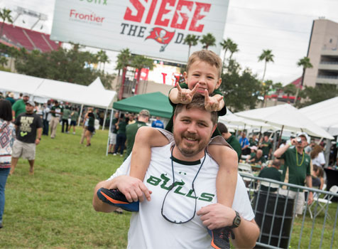 A son puts his horns up while on his dad's shoulders at Raymond James Stadium