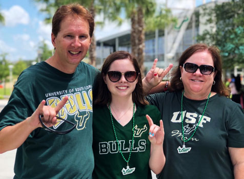 Parents and a female student in USF gear put their horns up