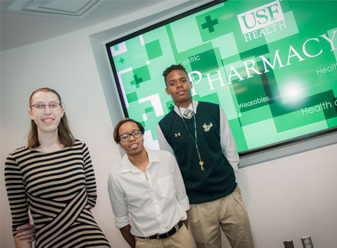 Three student interns from the USF Healht College of Pharmacy smile