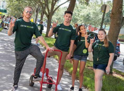 "Students on campus do the ""Go Bulls"" hand symbol"