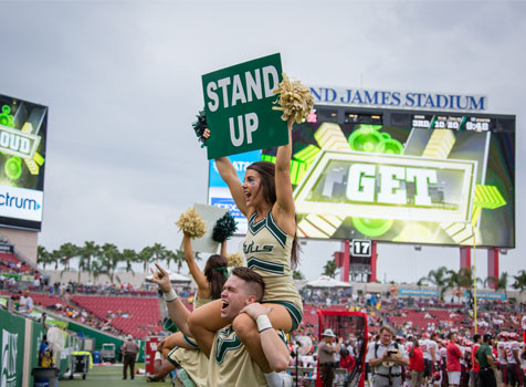Cheerleaders encouraging fans to stand up