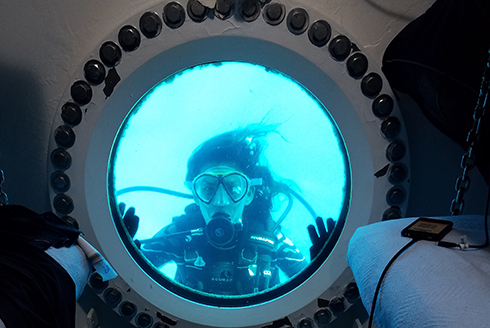 A scuba diver looking through a porthole window