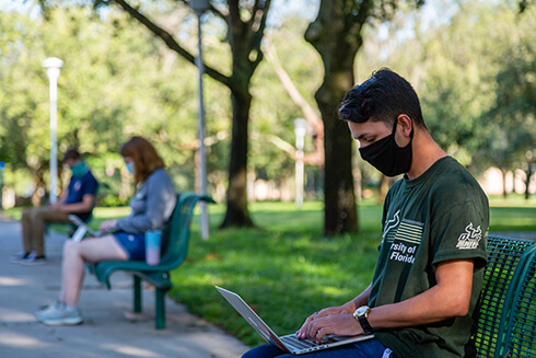 Three USF students wearing face coverings in MLK plaza at the Tampa, FL. campus.