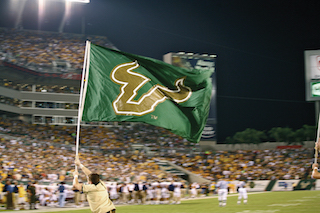 Person runs across the football field carrying a flag with the USF Bull U